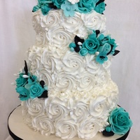 Rosette Cake With Turquoise Roses Cake is vanilla w, bc icing and bc rosettes. Gumpaste turquoise roses with black and white gumpaste accent leaves and flowers.