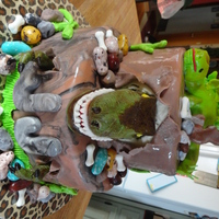 "Dinosaurs 8"" & 6"" round cakes covered in MMF. T-Rex head & stegosaurus is RKT covered in MMF & painted with food coloring. T-..."