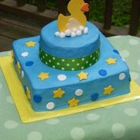 Ducky W/ Dots And Stars Buttercream w/ fondant dots, stars and bubbles. Duck is wooden (storebought). Border is ribbon.
