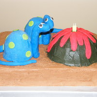 Sams Dinosaur Cake My son's 4th bday cake. Dinos are mini wondermold cakes covered in fondant. Volcano was a half ball, all iced in buttercream. We put 4...