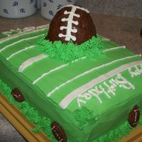 Football Cake Layered yellow and chocolate cake with choc. mousse filling, bc icing and the football is made out of rice krispies and covered with...