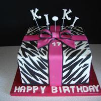 Zebra Gift Box Buttercream square with fondant/gumpaste zebra stripes, fondant gumpaste ribbon and bow. Gumpaste letters.