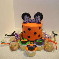 Minnie Mouse Theme In Halloween Colors Small buttercream covered cake with fondant gumnpaste bow, ears and dots. Cupcakes with fondant decorations and chocolate chip cookies.