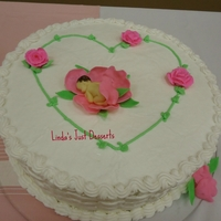 Gumpaste Baby Girl Wrapped In A Gum Paste Rose Ccake Butter cream iced white cake with gum paste baby.