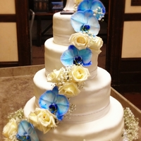 Blue Orchid & White Rose Wedding Cake This is my first wedding cake and I am ALMOST happy with it. The weather changed drastically the day before/of the wedding and started to...