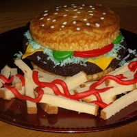 "Cheeseburger My 9 yr old requested a cheeseburger cake for his birthday. White 6""cake cut in half horizontally. Burger patty is a 6"" round..."