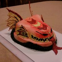Dragon Head Dark chocolate Dragon Head......Buttercream, airbrushed with White Chocolate Earrwings eyes and tongue...