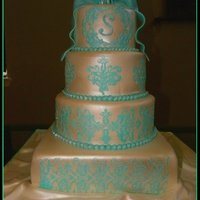 "Carla  12"" square topped with 10/8/6"" rounds; WASC with white chocolate SMBC and raspberry filling, covered in fondant, stenciled with..."