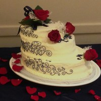 Roses Are Red, Scrolling Is Blue...this Cake Says I Love You 3 tier oval cake with buttercream icing and navy blue scroll work. Decorated with red roses and baby's breath (wrapped ends). 3 roses...