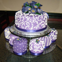 1320615293.jpg Purple cake with purple calla lilies with mini cakes. Top cake is carrot cake with cream cheese frosting. Bottom mini cakes are cheesecakes...