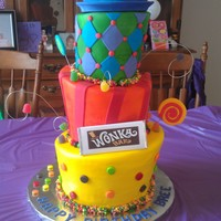 Willy Wonka Birthday  Four tiered cake. First three are rainbow layer cake and the top hat is styrofoam covered in fondant. Borderes are nerd ropes and...
