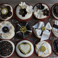 Black/white And Gold Themed Cupcakes These are Red Velvet Cupcakes decorated with some black and white fondant decorations accented with gold for a birthday celebration.