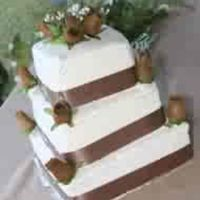 Brown Wedding Cake three tier wedding cake with a brown ribbon with brown roses.