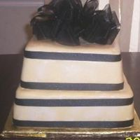 Gold & Black Wedding Cakes this is a two tier wedding cake. gold and black cake with sation ribbon with a bow with mmf.