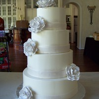 White With White Roses multi flavor cake tiers with buttercream icing. Gumpaste roses and fondant ribbon.