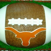 Football Texas Longhorns Medium sheet cake with a football pan cake on top All buttercream except the laces and stripes and the logo are fondant.