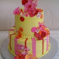"Yellow With Whimsical Flowers 9/6"" covered in buttercream with fondant stripes, dots and flowers. Painted the flowers with food coloring and gin."