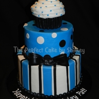 Masculine Cupcake Cake  A masculine version of the cupcake cake. Iced in buttercream, fondant decorations. Looking at the picture, I just realized that I put the...