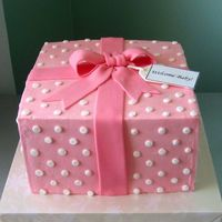 Pink Gift Box White cake with SMBC filling and Sugarshack's buttercream on the outside for smoothness. Pink fondant ribbon, white buttercream dots,...