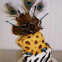 1321417664.jpg This was my first Topsy Turvy cake. Top tier chocolate fudge bottom tier chocolate and white marble. Hand painted animal prints numbers...