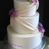 Elegant Ivory Wedding Cake With Fondant Swag And Purple Peonies