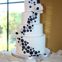 Black Button Wedding Cake   4 tier cake with a taller bottom tier, it has a variety of buttons in black finishes, it has 2 sugar flowers.www.sweetcakesbyrebecca.com