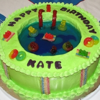 Pool Cake   cake made with blueberry jello, buttercream icing, gummy bears, gummy lifesavers, airheads and licorice.