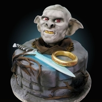 Lord Of The Rings Cake  9 inch round cake, with Orc bust ontop, hand carved out of styro foam so the weight was not too heavy on top of the cake, covered in...