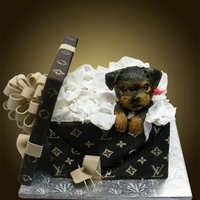 Puppy In A Louis Vuitton Gift Box Fondant puppy, about 5 inches, with fondant lid, loop bow and ribbons, the cake portion is the gift box. Hand painted gold detail.