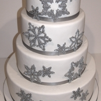 Sparkly Snowflake Wedding Cake Handmade gum paste snowflakes detailed with royal icing and silver disco dust. Cakes were red velvet, chocolate and vanilla