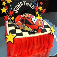 "Lightning Mcqueen Tire Cake This is a 8"" square cake draped with MMF. McQueen and the tire are both rice crispie treats covered in fondant and decorated with..."