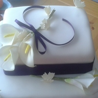 Simple Elegance Ivory cake with white call a lillies and ivory butterflies. Only my second time at making a wedding cake.