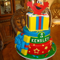 Elmo Cake 12 and 10 inch rounds coverd in fondant. Gift box on top was a 6 inch square cake dummy. All decorations are made of fondant. TFL