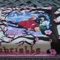 Inuyasha Japanese Anime Cake Chocolate cake with cherry filling. Covered in bc & Duff fondant. Fudge icing for piping of tree. Fondant cherry blossoms. Edible image...
