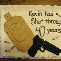 Gun And Target Birthday Cake  Sheet cake topped with fondant gun, bullets and target. All were exact replicas of the items used for competition shooting matches for the...