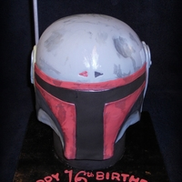 "Bobo Fett Helmet Carved cake on a 6"" round dummy cake for support. All fondant decoration with some painted on details."