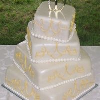 Wedding Cake 4 tier square white cake covered in pearl MMF with royal icing scroll work which was painted with gold luster dust.