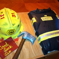 Fire Fighter's Retirement WASC firecoat iced in vanilla BC/ MMF, Chocolate fudge hat, iced in vanilla BC/MMF, cereal treat axe, fondant message board and flames.