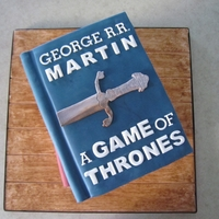 Game Of Thrones Book Cake For my FIL. A raisin spice cake, vanilla BC, all fondant covering/accessories. We gave him an e-reader for his bday, and he is currently...