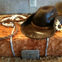 Western Cake Hay bale with cowboy hat, horseshoe's, lasso and belt buckle.