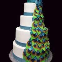 Peacock Wedding Cake This is a 4 tier wedding cake with a hand sculpted rice krispie peacock topper. The feathers are fondant.