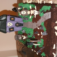 Halloween Graveyard Sheet cake with candy and fondant decorations, and a Wilton gingerbread haunted house.