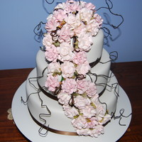 Round Wedding Cake With Pink Roses 3 tier Round cake with Pink paper roses. Chocolate mucake top and bottom, middle was caramel mudcake.
