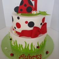 Ladybug First Birthday Cake White almond sour cream cake with raspberry filling and chocolate cake, iced in buttercream with fondant accents.