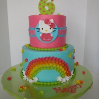 Rainbow Hello Kitty Cake Cheescake cake with strawberry filling and chocolate/chocolate chip cake, iced in buttercream with fondant accents.
