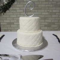 Quilted 2 tier round, white almond cake with white fondant, quilted pattern and fondant pearl border.