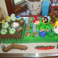 Angry Birds Cake For Grandson Andrew (6) Cake depicts an Angry Birds game. Birds with slingshot are on the right. Pigs and captured bird eggs are on the left.