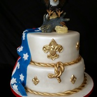 Eagle Scout Cake Fondant covered 10 and 12 inch cake with fondant accents. Topper is a ceramic eagle the client purchased.