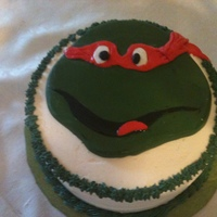 Raphael Teenage Ninja Mutnat Turtl Cake is simple round layer cake with buttercream icing; Raphael's head is fondant.
