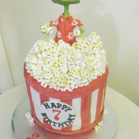 Rango Movie Cake   Fondant Covered Popcorn bucket with mini marshmallow popcorn and a rice treat Rango coved in modeling chocolate.